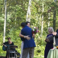 bride and groom dancing in the meadow by the pond